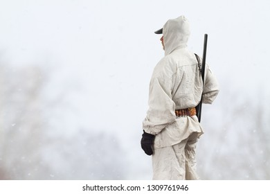 hunter in white camouflage with shotgun stands in the winter field