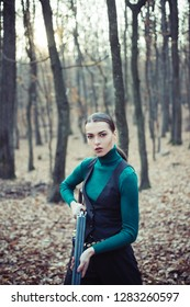Hunter woman. Hunter with a backpack and a hunting gun. Hunting period, autumn season. Female with a gun. A hunter with a hunting gun and hunting form to hunt