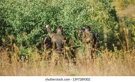Hunters friends enjoy leisure. Teamwork and support. Activity for real men concept. Hunters with rifles in nature environment. Hunters gamekeepers looking for animal or bird. Hunting with friends.