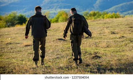 Hunters friends gamekeepers walk mountains background. Hunters rifles nature environment. Hunter friend enjoy leisure. Hunting with partner provide greater measure safety often fun and rewarding.