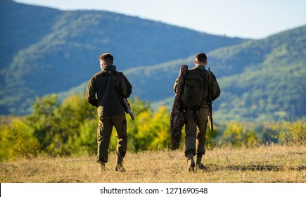 Hunters friends gamekeepers walk mountains background. Hunting with partner provide greater measure safety often fun and rewarding. Hunters rifles nature environment. Hunter friend enjoy leisure.