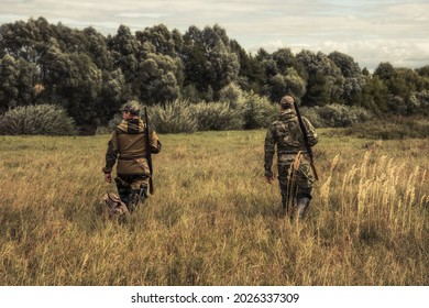 Chasseurs traversant un champ rural vers la forêt pendant la saison de chasse