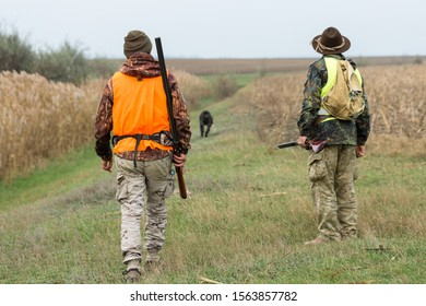 A hunters with a gun in his hands and a hunting dog in a reflective orange vest hunts a pheasant in the steppe. The view from the back.