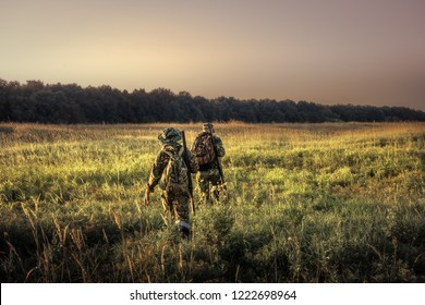 Hunters with hunting equipment going away through rural field towards forest at sunset during hunting season in countryside