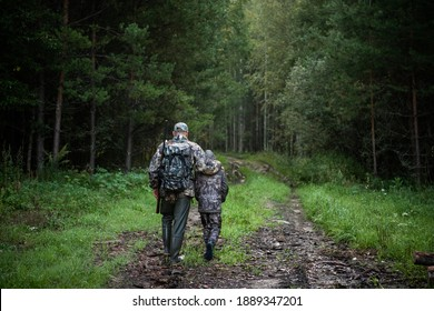 Hunters with hunting equipment going away through rural forest at sunrise during hunting season in countryside.