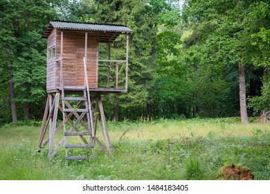 Hunters hut in the forest by the road. Hunter tower or watch post in the wilderness. Hunter post is a wooden structure to watch and shoot at wild animals