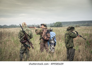 Hunters preparing for hunting in rural field in overcast day during hunting season