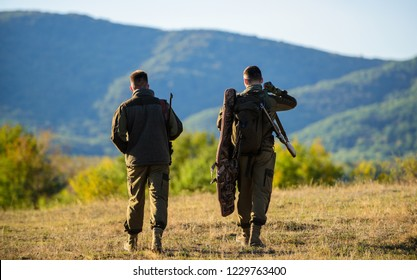 Hunters rifles nature environment. Hunter friend enjoy leisure. Hunters friends gamekeepers walk mountains background. Hunting with partner provide greater measure safety often fun and rewarding.