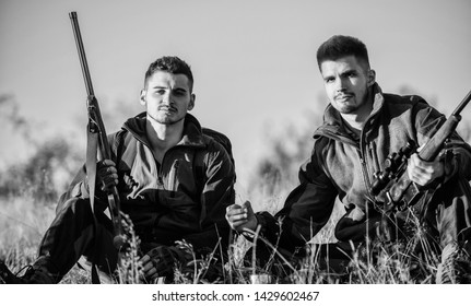 Hunters with rifles relaxing in nature environment. Hunters satisfied with catch drink warming beverage. Hunters friends enjoy leisure. Rest for real men concept. Hunting with friends hobby leisure.