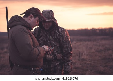 Hunters spot their position via smartphone in rual field during hunting season