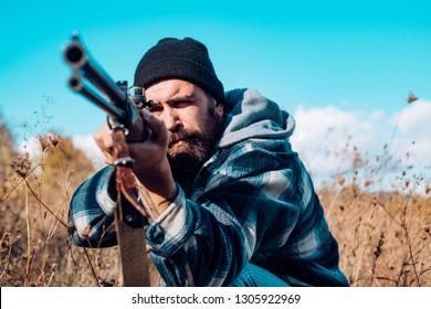 Hunting in America. Hunter with shotgun gun on hunt. Hunter aiming rifle in forest. Hunter man. Hunting period, season. Male with a gun