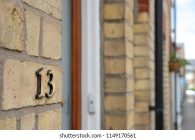 Hunting, Cambridgeshire, UK - Circa August 2018: Shallow focus view of a brass number 13 number seen attached to the entrance of a brick-built terraced house in this english market town.