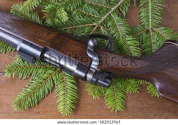 hunting carbine on fir branch and wooden background top view