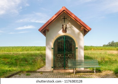 Hunting chapel. Rural wayside shrine in hunting style with deer antler and skull and decorative trellis. Bench by the field. Lower Austria. Burgenland. Central Europe.