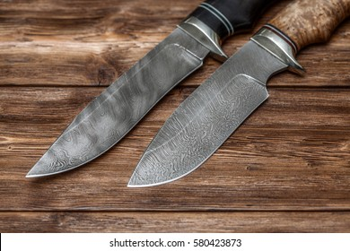 Hunting damascus steel knives handmade on wooden background, closeup