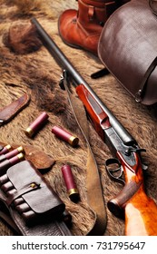 Hunting double barrel vintage shotgun, leather bandolier hunters bag,knife and leather boots mmunition, on the wild boar furs, close-up.Copy space.Concept hunting