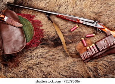 Hunting double barrel vintage shotgun, hunters bag,leather bandolier mmunition, on the wild boar furs, close-up.Copy space.Concept hunting