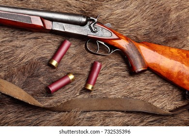 Hunting double barrel vintage shotgun and leather bandolier ammunition, on the wild boar furs, close-up.Copy space.Concept hunting