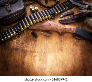 Hunting equipment - pump action shotgun, 12 mm hunting cartridge  and hunting knife on the wooden table.