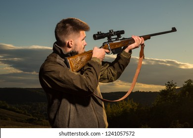 Hunting Gear - Hunting Supplies and Equipment. Hunter with shotgun gun on hunt. Hunter with Powerful Rifle with Scope Spotting Animals