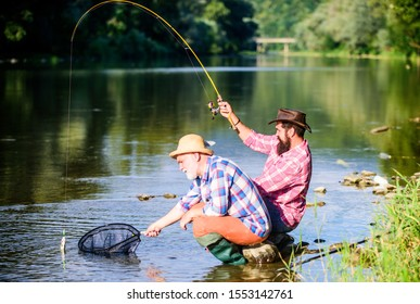 hunting. happy fishermen friendship. Catching and fishing. Two male friends fishing together. retired dad and mature bearded son. fly fish hobby of men in checkered shirt. retirement fishery.