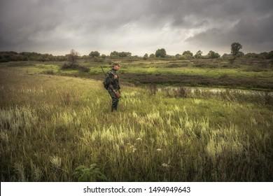 Des chasseurs armés se tenant dans le champ près de la rivière pendant la saison de chasse, le jour de la chasse