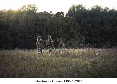 Hunting hunters in  rural field nearby forest at sunset during hunting season