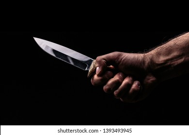 Hunting knife in hand on dark background