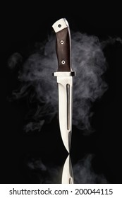 Hunting knife with smoke on a black background