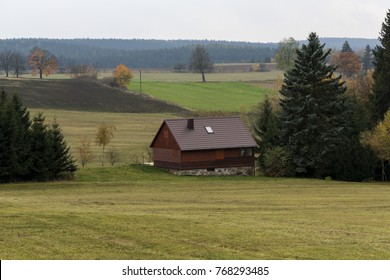 hunting lodge on a meadow near a deep spruce forest on the Czech Highlands