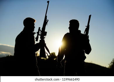 Hunting with partner provide greater measure safety fun and rewarding. Hunter friend enjoy leisure. Hunters friends gamekeepers with guns silhouette sky background. Hunters rifles nature environment.