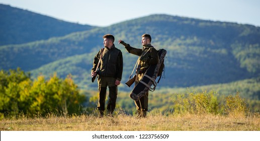 Hunting with partner provide greater measure safety often fun and rewarding. Hunter friend enjoy leisure. Hunters friends gamekeepers walk mountains background. Hunters rifles nature environment.