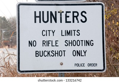 A hunting regulation sign is posted at the edge of city limits. According to regulations, hunters  must use buckshot only in the city.