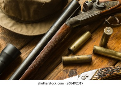 Hunting rifle, ammunition, a knife and a cap on the wooden table, close-up