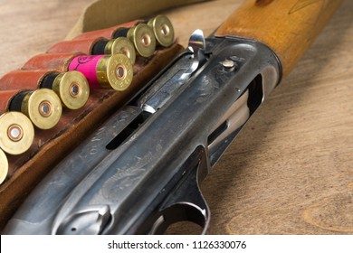 Hunting rifle and ammunition lie on wooden background.