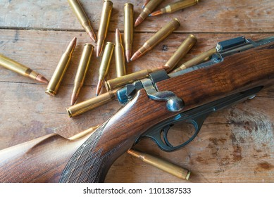 Hunting rifle with bullets on old wooden background