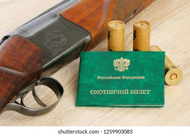 Hunting rifle with cartridges and certificate «Hunting permit Russian Federation» lying on a wooden table. Closeup view.