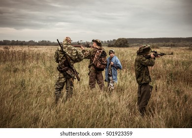 Hunting scene with hunters aiming during hunting season in rural field in overcast day with moody sky
