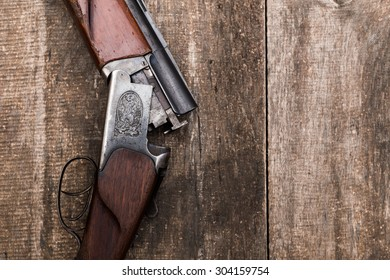 Hunting shotgun and ammunition on wooden background