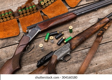 Hunting shotgun, ammunition on wooden background