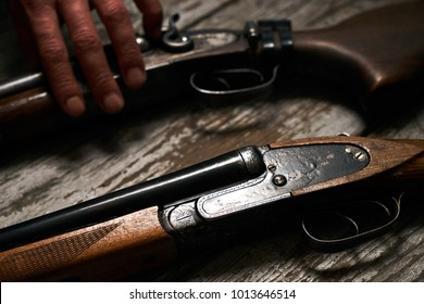 Hunting shotgun riffle on old rustic wooden table