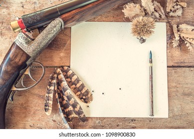Hunting stories concept: hunting rifle, target upsite down, pheasant feathers and vintage pen on old wooden background
