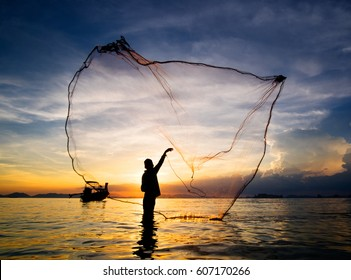 Hunting for Sunset. Silhouette of fisherman throwing fishing net into the sea, Krabi, South Thailand.