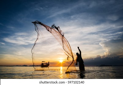 Hunting for Sunset.  Silhouette of unidentified fisherman throwing fishing net, Thailand.