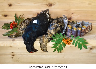 hunting trophies (three downed blackcocks) lie on a wooden table with Rowan berries