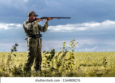 Hunting for wild animals. Hunter with a gun on the field on a cloudy sky background