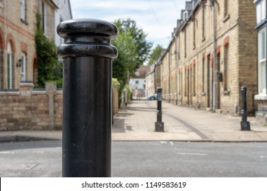 Huntingdon, Cambridgeshire, UK - Circa August 2018: Low level, shallow focus of black-painted safety and vehicle throughway prevention send at the entrance to English terraced houses in a town.