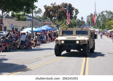 HUNTINGTON BEACH, CA - JULY 4: Military vehicle with flags drives along Huntington Beach July 4th parade route