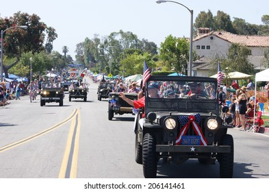 HUNTINGTON BEACH, CA - JULY 4: Military vehicle carrying world war II veterans drives along Huntington Beach July 4th parade route