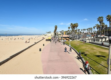 HUNTINGTON BEACH, CA - MARCH 25, 2015: Boardwalk and Sand Volleyball Courts. The boardwalk, near the pier, accommodates strollers, skaters and bicycles.